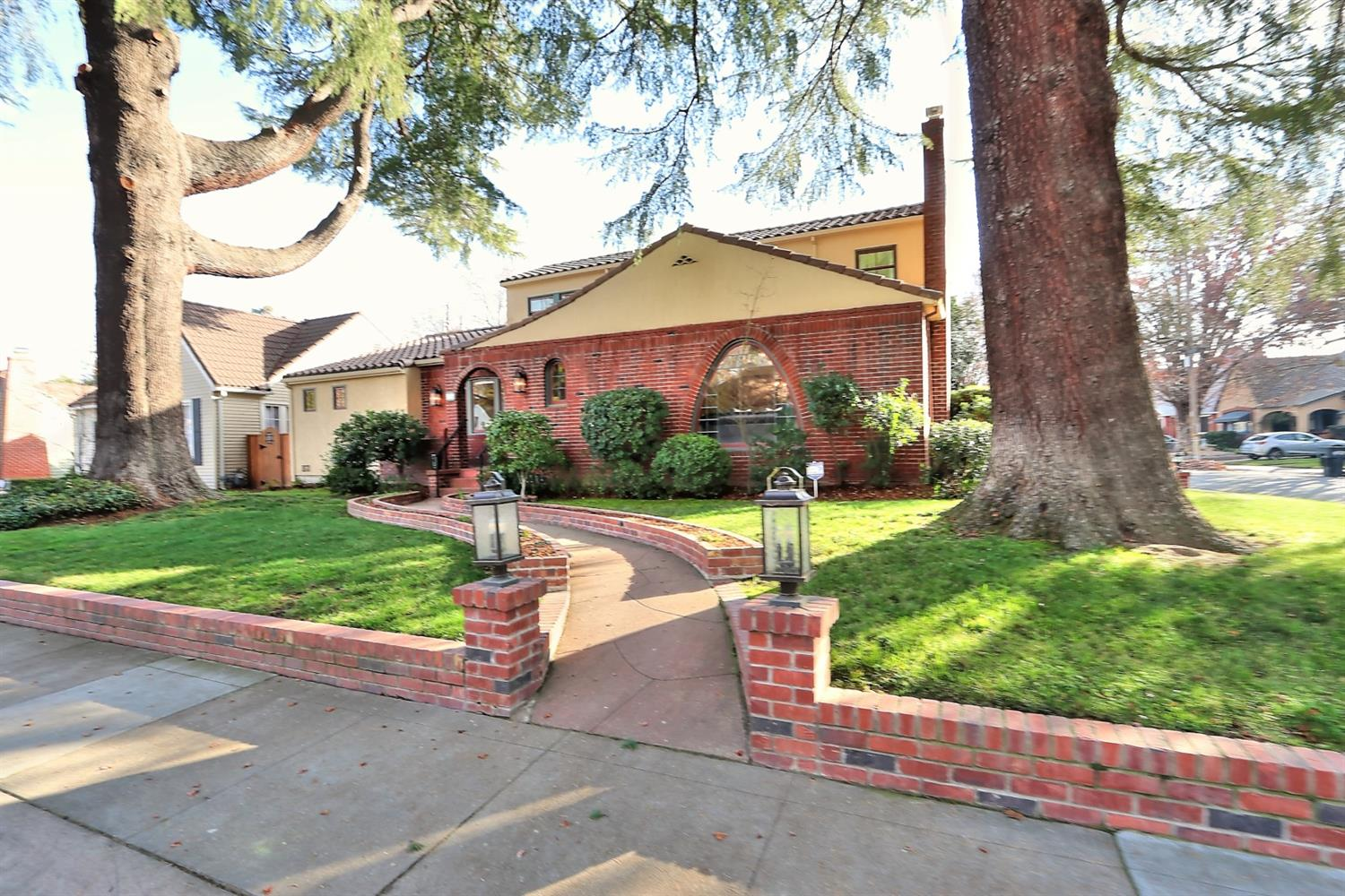 Stunning Brick Mediterranean in Curtis Park - Original features with all the updates, arched doorways, leaded glass windows, hardwood floors with inlay, 3 cozy gas fireplaces and original built-ins. 4 good size bedrooms with big closets, 2.5 baths ready to move in! Bright kitchen(remodeled 2016)has quartz countertops, stainless appliances, breakfast bar and wine frig. Opens up to the family room along with built-in office space and access to the back deck. The downstairs private master suite(addition 2018)has cozy gas fireplace a view of the yard. Big master bath with his/hers sinks & Bubble tub, plus walk in shower. Upstairs you will find 2 bedrooms and 1 full updated bath.  Nicely landscaped with 2 amazing Heritage trees-Deodar Cedars in