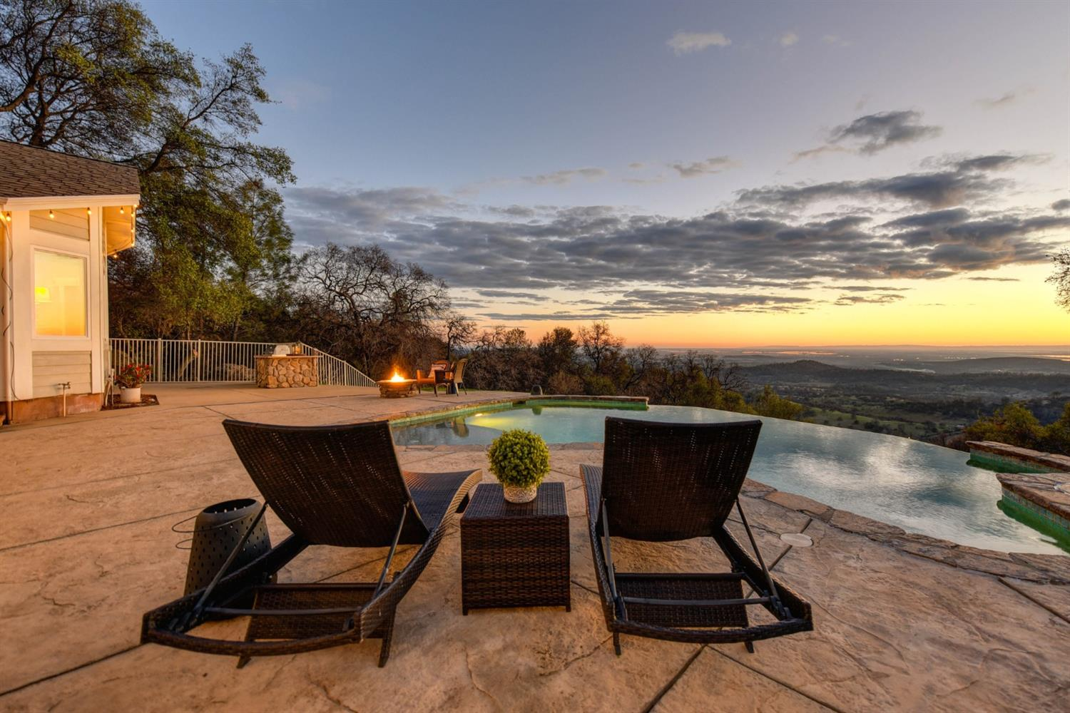 Amazing mountaintop retreat on 20 beautiful acres in Browns Valley! This exquisite getaway has stunning views of the sunset over the Sutter Buttes, Mayacamas Mountains, the Sacramento Valley, and beyond. The custom home is powered by owned solar (and a backup partial house generator) and boasts an open floor plan, remodeled kitchen and bathrooms, and a long list of amenities. The backyard features an infinity edge pool, built-in BBQ, redwood deck, and covered patio, all designed to take in the incredible views. Nestled on the parklike grounds is a greenhouse, garden beds, fruit trees, and a ~2,600 sq. ft. shop with electrical and plumbing for easy conversion to a possible studio living space. The property also has irrigation water available