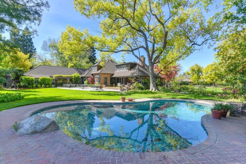Charming Carmel style Tudor home on a picturesque .69 acre garden filled parcel in the heart of Old Sierra Oaks! One of the finest locations in Sacramento County, this property has been lovingly cared for and adored. Memories of fun & frolic from school graduations, pool parties and all the holidays have been enjoyed here. Well designed, comfortable rooms are finished with wood paneled walls, coffered beam ceilings, hardwood floors, handsome millwork, built-in cabinetry and picture windows with amazing views of the gardens and pool. Majestic heritage oak trees gracefully shade the property and surround the pool providing a visual treat from the many picture windows. The chef's kitchen is updated and flanked by the sunny breakfast nook and f