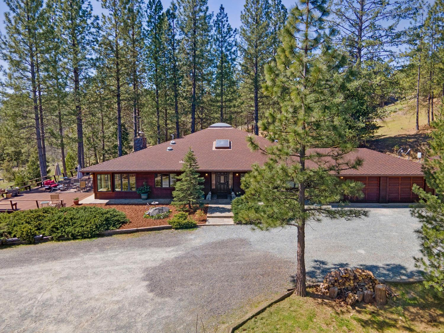*Price change*---Check out this UPSCALE HORSE PROPERTY ON 26.4 ACRE with an  UPDATED CONTEMPORARY RANCH Style Home. NESTLED AMONG TOWERING PINES with clear views of the moon & stars at night. The ENTRY leads to the amazing DINING area with beautiful REDWOOD BEAMS &  above. SKYLIGHT. The LIVING ROOM features CATHEDRAL ceilings, a GRAND FIREPLACE,built in cabinetry. The OPEN & SPACIOUS KITCHEN features granite counter tops,plenty of cooking and prep space, breakfast room with a view,walk-in pantry, & 2 center islands. Each bedroom has it's own bathroom SUITE. There's 2 hot water heaters, 2 AC & Heating units, 2/5K gallon tanks for well water. The MD Barn is set up with 4 stalls open to corral, hot water heater, shower, washer/dryer, covered paddocks, front porch, arena,acres of dividable corral enclosed with Electro Braid wire cross fencing, plus a heated chicken pen. This QUALITY-BUILT home in this MAGICAL MOUNTAIN SETTING is waiting for you.