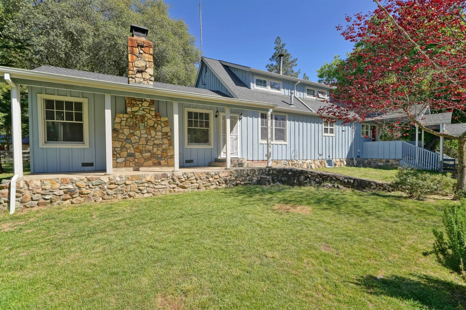 Rustic charm abounds at this ranch home in foothill wine country w/ fully fenced usable 2.5 acres & seasonal creek. Covered country front porch leads to gorgeous great room w/ knotty pine T&G open beamed ceiling & unique custom milled wood floors. Finishing touches incl a wood burning fireplace insert & rock surround, large picture window & custom built-in bookshelves & cabinets. Alley style kitchen w/ granite counters, butcher block prep sink & dining bar. Home has 4 bdrms, 2 downstairs & 2 upstairs. Bring your animals & hobbies! Property has a 2-car detached garage w/ workshop, outbuilding w/ bath & potential for kitchen that could be guest house/in-law quarters, chicken coop, fenced garden, & a variety of trees incl walnut, apple, oak, s