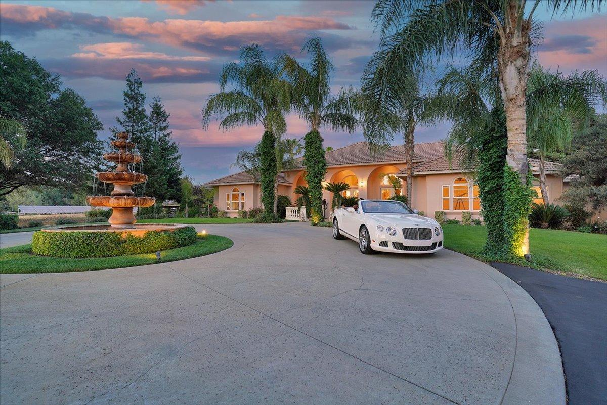 Escape from life's demands and be inspired by the private and tranquil Sierra foothills setting, manicured landscapes, flowing lagoons, and seemingly endless sunset views. Featuring a gated palm tree-lined entrance, expansive 5-acre parcel awaiting a future vineyard, special event parking, and limitless entertainment opportunities. This inviting residence is bright and open with a flowing single-level floor plan extending to an outdoor entertaining oasis. Featuring a professional Wolfe/Miele kitchen, elegant granite slab counters and walk-up bar seating. Your master retreat awaits with a spa-like atmosphere, retreat seating, walk-in closet, and private courtyard with scenic views. This 52-panel Solar residence offers a 2nd master bedroom with separate entrance, a beautiful sunroom, large family bedrooms, home office with pool view, dual dining rooms, travertine flooring, electric vehicle charging station, and endless luxurious amenities. Welcome Home!